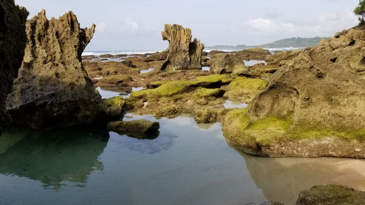 Water pools by the rock formations at the end of the beach