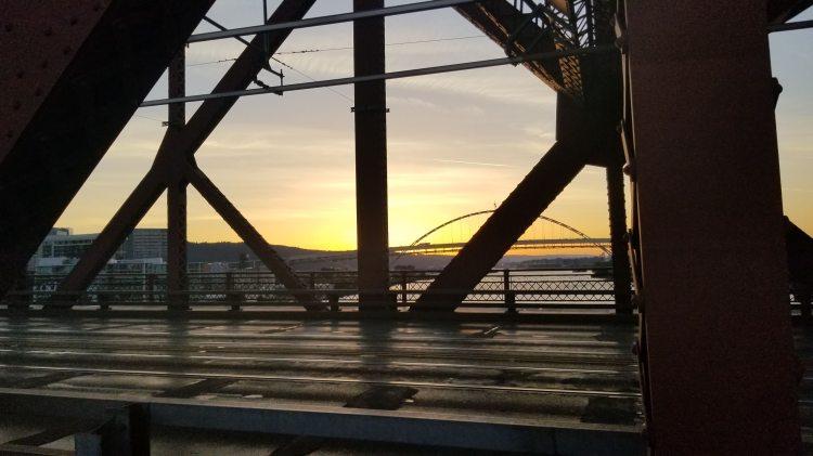 Walking across the Broadway Bridge at sunset