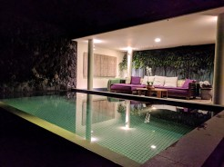 Outdoor seating and pool at night in the Bamboo 2 Villa