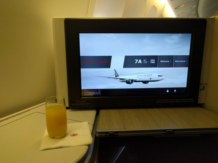 Enjoying a flight delay in business class with a mimosa
