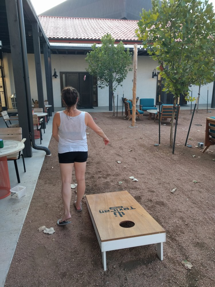 Max playing corn hole at Texican Court