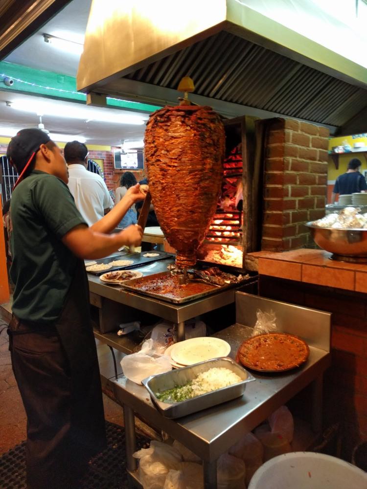 The al pastor tacos being prepared at El Fogon