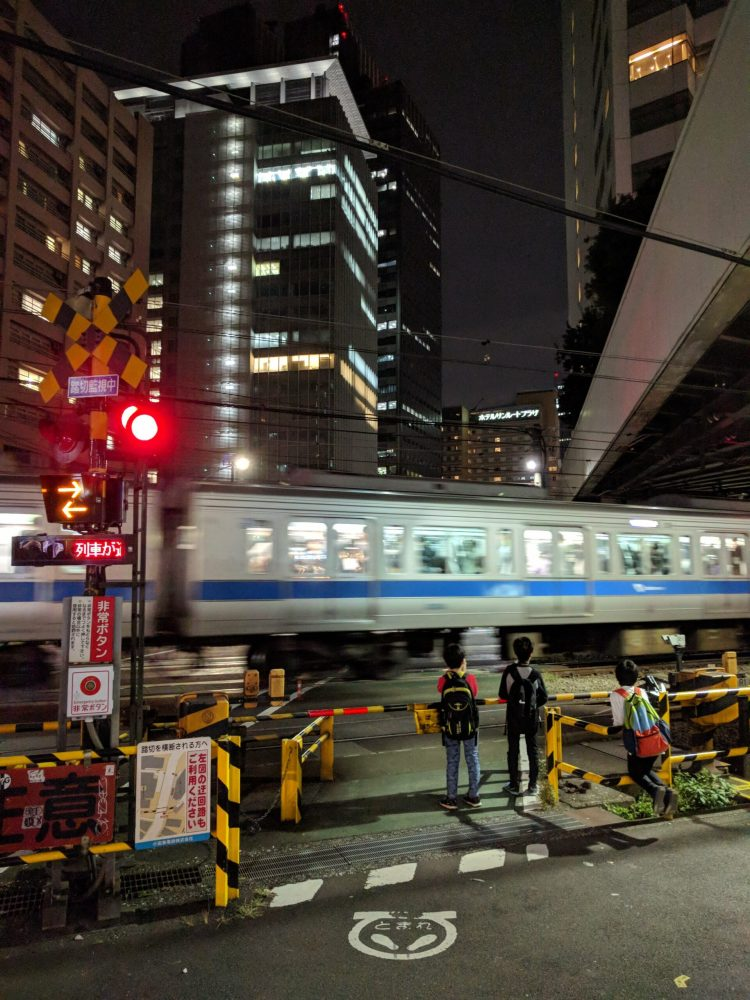 Waiting at a train crossing in Tokyo