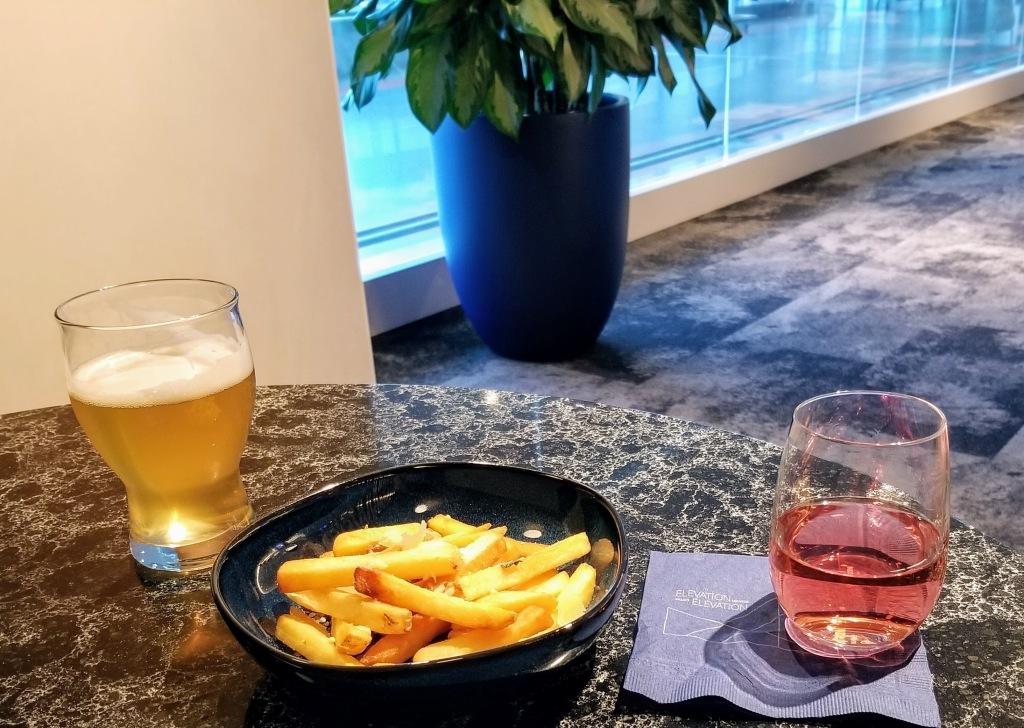 YYC WestJet Elevation Lounge: WestJet Elevation beer (left) and Road 13 sparkling rose (right) with truffle fries
