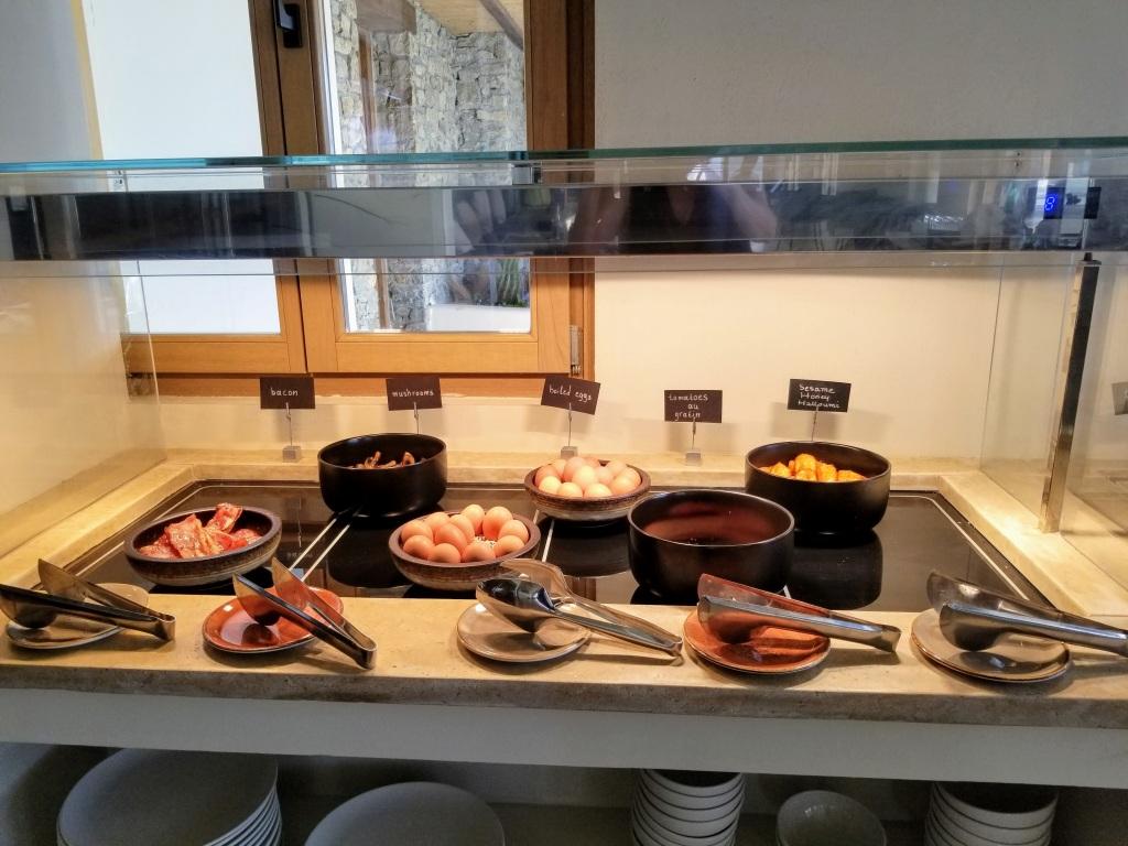 Aegon Mykonos: Breakfast buffet options like hard-boiled eggs, bacon, sausage, and grilled halloumi