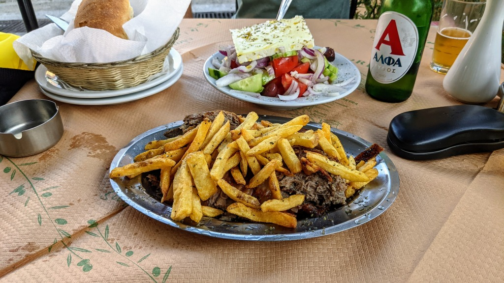Giannitsiss: portion of lamb and chips, Greek salad, and bead