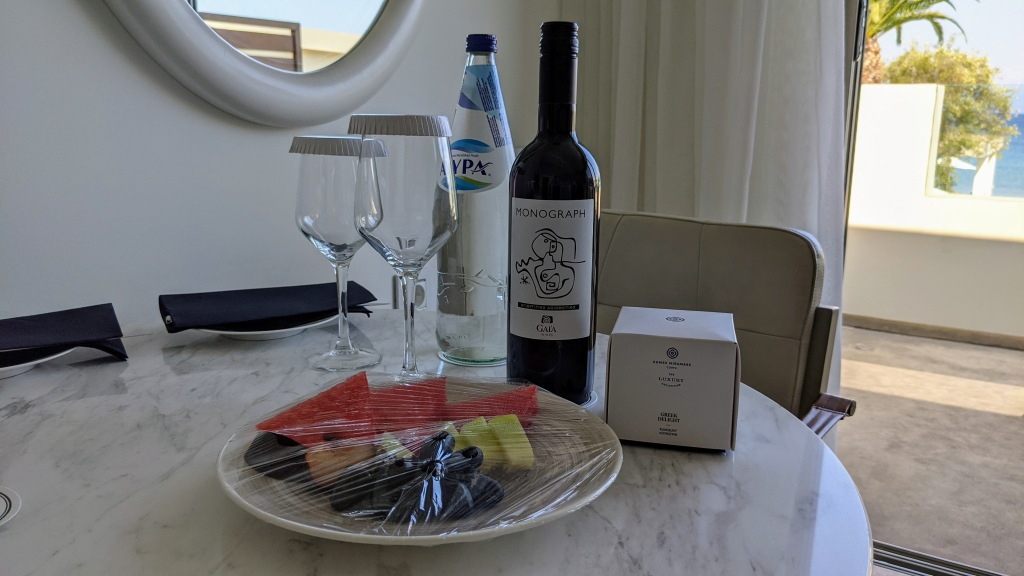 Domes Miramare Corfu: Welcome treats! A bottle of sparkling water, a bottle of red Greek wine, a fruit plate and kumquat Greek delight sweets